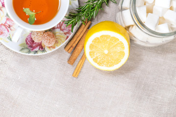 Cup of black or red tea with lemon, rosemary, mint, cinnamon sticks, sugar on grey tablecloth, top view