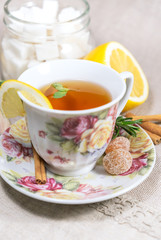 Cup of black or red tea with lemon, rosemary, mint, cinnamon sticks, sugar on grey tablecloth