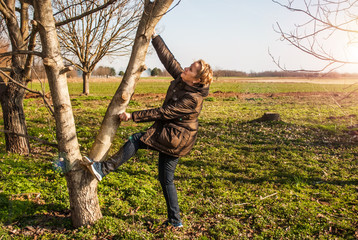 Middle-aged women, young spirit, climbing a tree, enjoying the sunny day and the arrival of spring