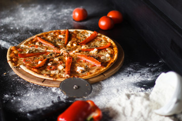 Delicious pizza with cheese and vegetables on black background.