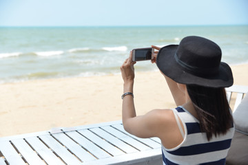 Beautiful woman holding smartphone,take photo,happy and smile,with sea and sky, Pataya inThailand.