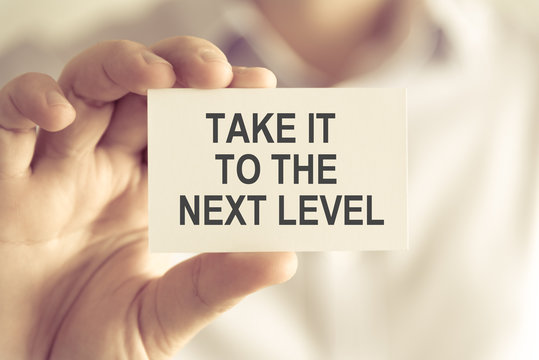 Businessman holding TAKE IT TO THE NEXT LEVEL message card