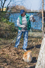 A man works in the garden, fires a bonfire, removes, cleans the territory, cuts dry branches with his little red dog near blue river