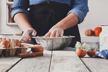 Woman baker knead yeast dough with eggs and flour