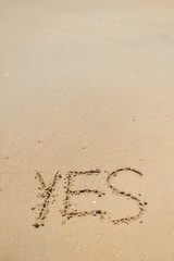 Yes sign written in sand on beach texture top view close up