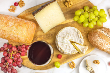 Red wine, cheese, bread and grapes at tasting