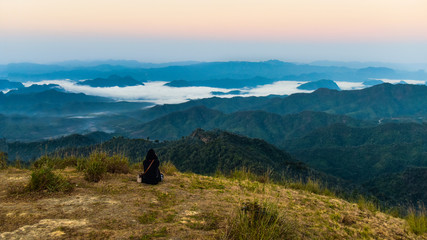 Woman site on the rock on top of cliff to see  sea of mist at Thu Le Province of Thailand