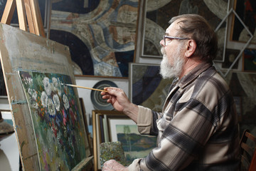 Elderly painter with beard and glasses draws a flowers picture by oil paint in art workshop