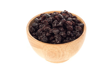 Dried raisins in wooden cup on white background.
