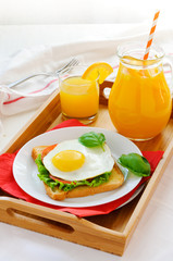 Sandwich with fried egg and orange juice