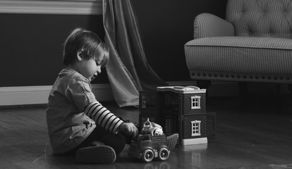 adorable toddler boy playing with toy cars inside home on ground