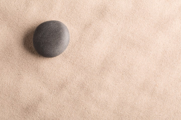 Acrylic Prints Stones in Sand minimalism zen background with black stone in sand. Yoga meditation or spa wellness theme.
