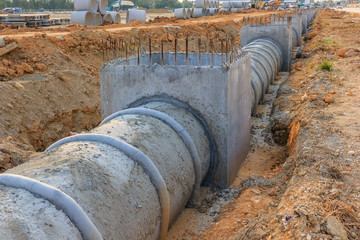 Concrete Drainage Pipe and manhole on a construction Site .Concrete pipe stacked sewage water system aligned on site