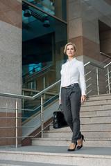 Beautiful business woman walking on stairs
