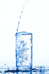 Water pours into the glass, monochromatic background, studio light