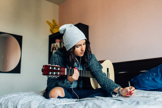 Young beautiful woman composing a song  sitting on her bed in the bedroom holding guitar - musician, songwriter, composer concept