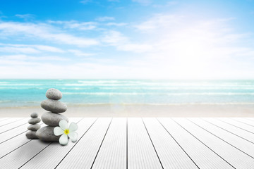 Stack of pebble stones and Plumeria at the beach on a wooden surface. Concept Zen, Spa, Summer, Beach, Sea, Relax.