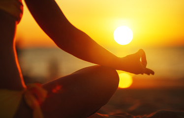 Fototapete - hands of woman meditating in yoga pose at sunset on beach
