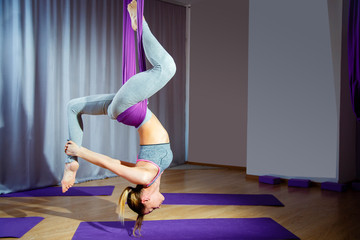 Young woman posing doing aerial yoga exercise with hammock upside down.
