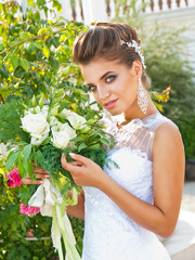 slender young bride in wedding dress outdoors