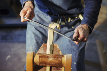 Midsection of carpenter shaving wood with drawknife at workshop