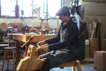 Side view of carpenter shaving wood with drawknife in workshop