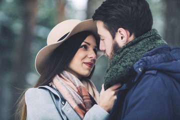 Close-up of romantic couple looking at each other in forest during winter