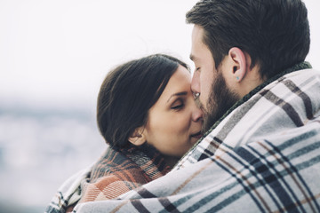 Close-up of romantic couple wrapped in scarf and kissing