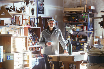 Portrait of confident carpenter holding drink while standing by table in workshop