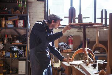 Carpenter examining wooden stool in workshop