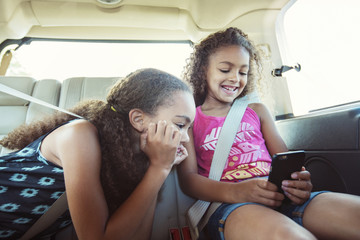 Girls looking at smart phone while traveling in car