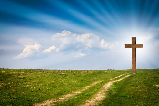 Jesus Christ cross, wooden crucifix on a scene with blue spring sky, green meadows, bright light, rays, clouds. Christian wooden cross on field with green grass and path leading to the cross