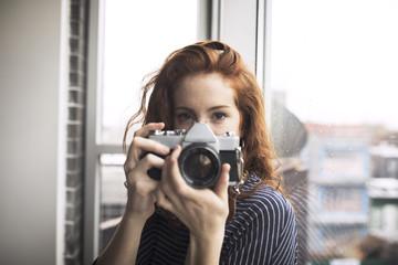Portrait of woman holding digital camera