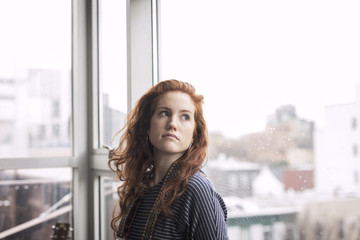 Thoughtful woman looking away while standing by window