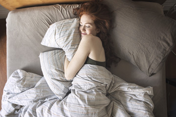 High angle view of smiling woman sleeping on bed at home