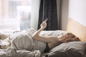 Woman using smart phone while lying on bed