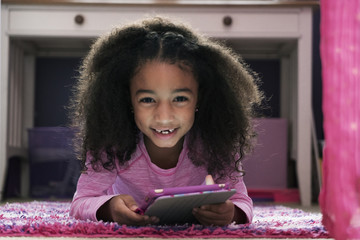 Portrait of smiling girl holding tablet computer while lying on rug at home