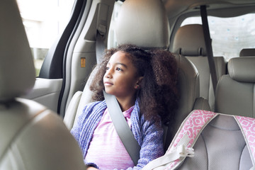 Thoughtful girl looking through window while traveling in car