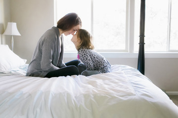 Playful mother with daughter on bed at home
