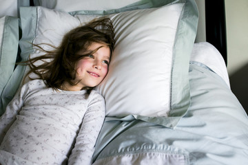 Smiling girl lying on bed at home