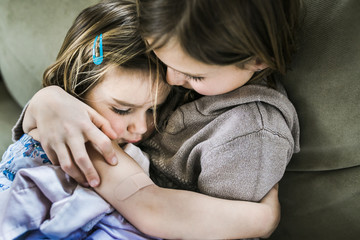 High angle view of girl embracing sister while sitting on sofa at home