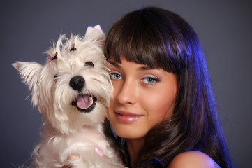 Caucasian prime adult female holding white terrier dog.