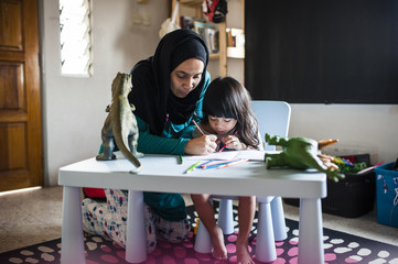 Woman assisting daughter in drawing at home