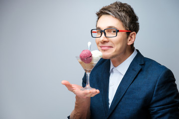 Handsome young man with glasses tastes ice cream balls in a transparent glass in the studio