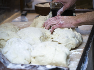 Baker kneading dough. Homemade bread. Hands preparing bread dough on a wooden table. Preparing traditional homemade bread. Man hands kneading fresh dough for making bread