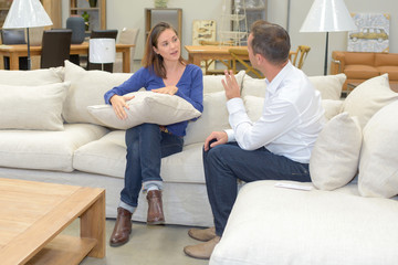 Couple sat on sofa in shop