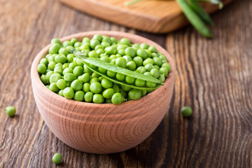 Green peas in wooden bowl on  rural background