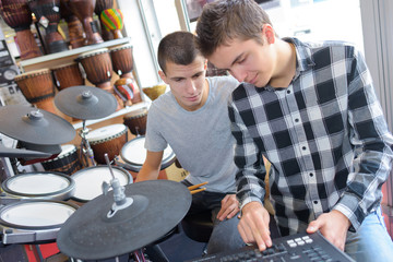 Young men looking at electronic drum machine