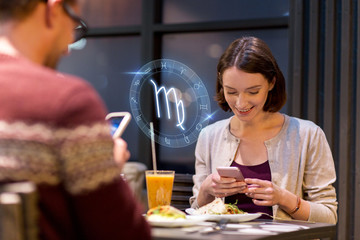 couple with smartphones and zodiac signs at cafe