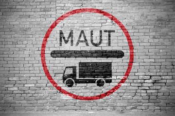 Ziegelsteinmauer mit Verkehrszeichen Mautpflicht nach dem BundesfernstraßenmautgesetzGraffiti